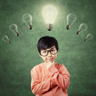 43903655 - cute little girl wearing glasses and standing under light bulb with thinking poses, shot in the class